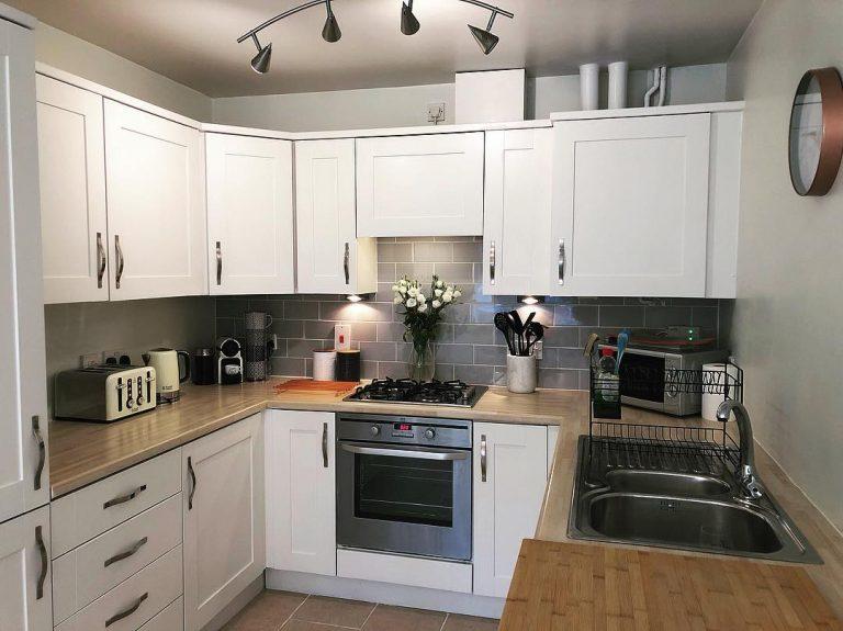 Cocina mediana con muebles blancos, pared gris y mármol ...